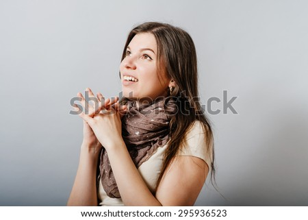 Young woman folded her hands in prayer. On a gray background. - stock photo