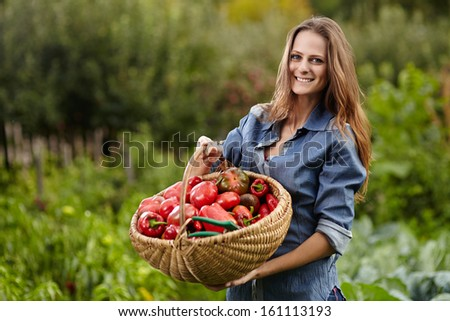 Young woman gardener holding a basket full of red paprika in her garden, selective focus - stock photo