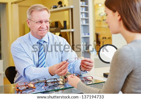 Young woman getting a consultation from an optician for new glasses - stock photo