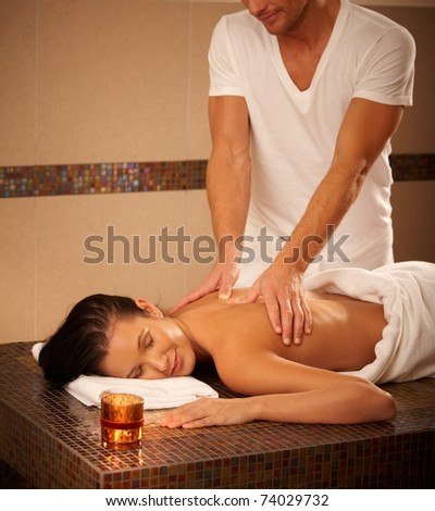 Young woman getting back massage in wellness center, relaxing with eyes closed.? - stock photo