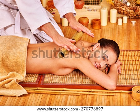Young woman getting bamboo massage. Male therapist with stick. - stock photo