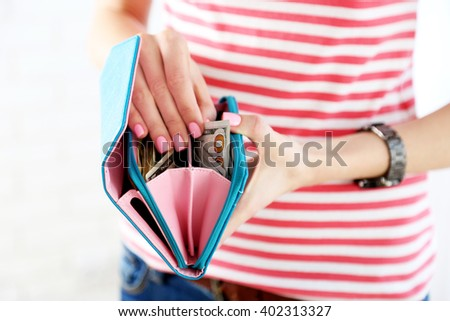 Young woman getting dollar banknote from purse - stock photo