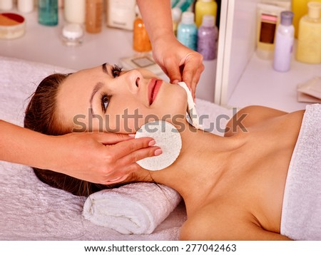 Young woman getting facial  massage in beauty spa. Towel under neck. - stock photo