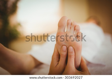 Young woman getting foot massage in therapy room - stock photo