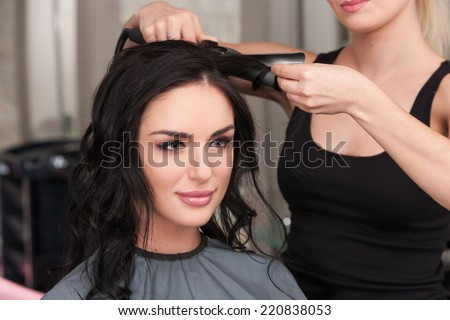 young woman getting her hair curled by stylist at parlor. Beautiful young hairdresser giving new haircut to female - stock photo