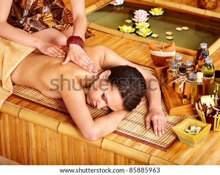 Young woman getting massage in bamboo spa. - stock photo