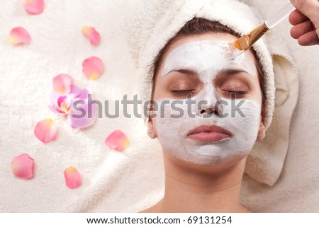 Young woman getting mud mask at spa-salon. - stock photo