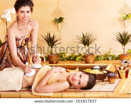 Young woman getting stomach massage in bamboo spa. - stock photo