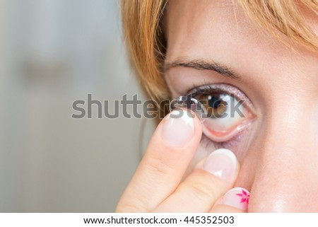 Young woman/girl putting contact lens in her eye close up with copy space . Selective Focus on lens. - stock photo