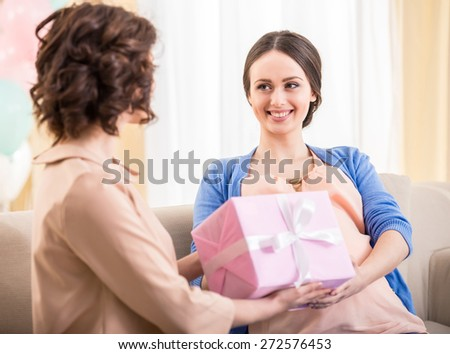 Young woman gives a gift to her pregnant friend. - stock photo