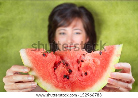 Young woman gives a piece of watermelon, top view, focus on watermelon - stock photo