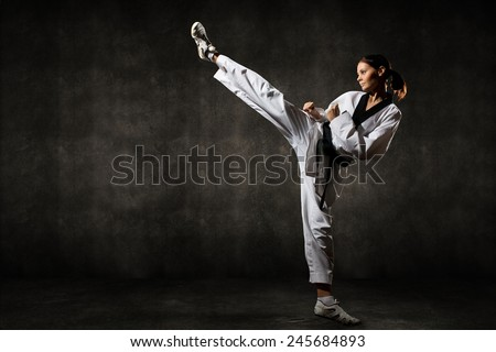 Young woman giving a kick on background - stock photo