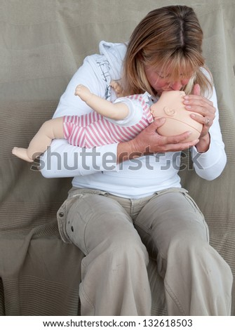 Young woman giving CPR to an infant - stock photo