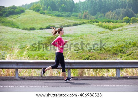 Young woman going for a run on a country road.  - stock photo