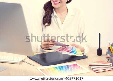 Young woman graphic designer using graphic tablet to do her work at desk - stock photo
