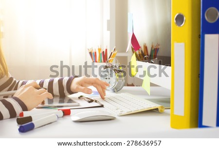 Young woman graphic designer using graphic tablet to do his work at desk - stock photo
