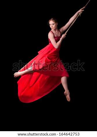 Young woman gymnast in red dress on rope on black background  - stock photo