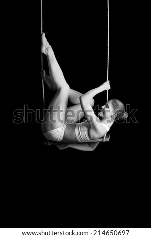 Young woman gymnast on a trapeze over black background  - stock photo