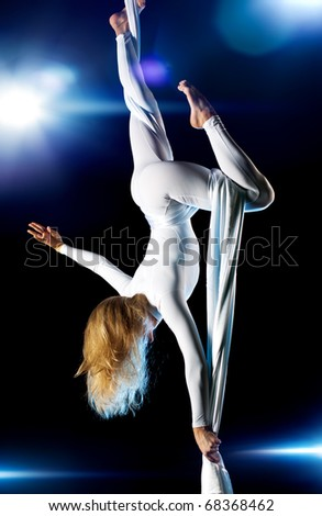 Young woman gymnast. On black background with flashes effect. - stock photo