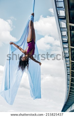 Young woman gymnast. On city and sky background. - stock photo