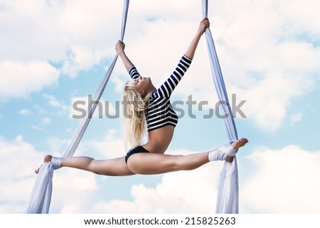 Young woman gymnast. On sky background. - stock photo