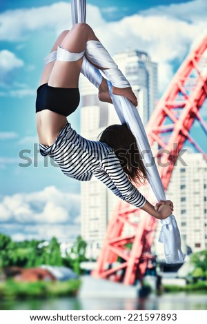 Young woman gymnast. On urban background. - stock photo