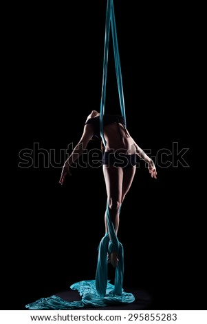 Young woman gymnast with blue gymnastic aerial silks isolated on black - stock photo