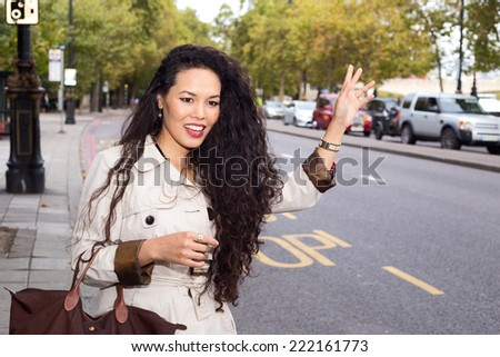 young woman hailing a taxi - stock photo