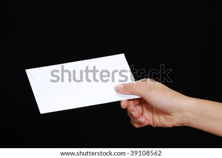Young woman hand holding an envelope isolated on a black background. - stock photo