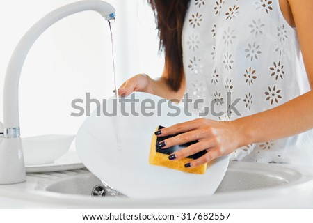 Young woman hands with nice manicure washing dishes in the sink in the kitchen using sponge with soap foam . Close up view. - stock photo