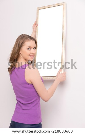 Young woman hanging mirror on wall. beautiful brunette standing near wall and looking over shoulder - stock photo