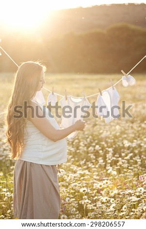 Young woman hanging up baby laundry - stock photo