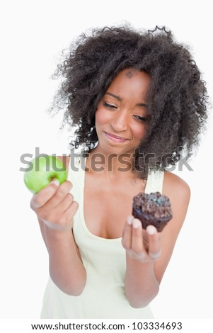 Young woman hardly hesitating between a chocolate muffin and a green apple - stock photo