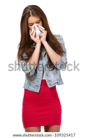 young woman has allergy and blowing her nose - stock photo