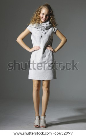 young woman has her hands on her hips and is posing for the camera. - stock photo