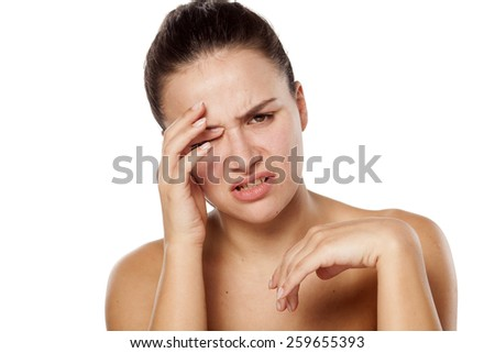young woman has pain in the eye - stock photo