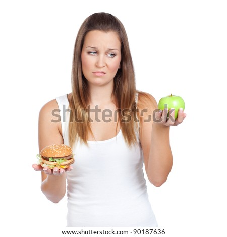 Young woman having a dilemma: greasy hamburger or an apple? Isolated on white - stock photo