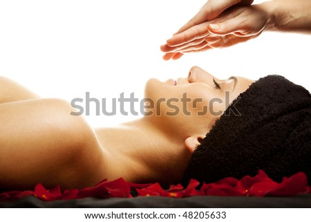 Young woman having a facial energy massage, isolated on white - stock photo