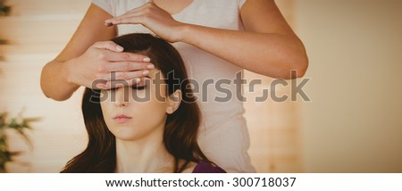 Young woman having a reiki treatment in therapy room - stock photo