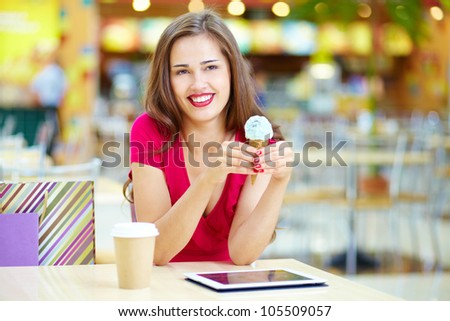 Young woman having a rest after shopping at the ice cream bar - stock photo