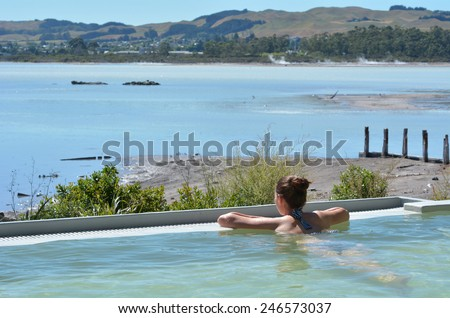 Young woman having a spa in outdoors hot pool in Rotorua, New Zealand. - stock photo