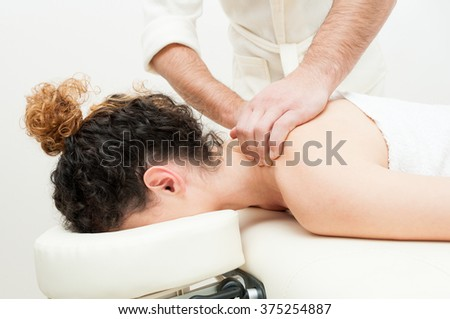 Young woman having back or shoulders massage in spa center as healthcare and body care concept - stock photo