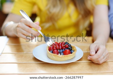 Young woman having custard fruit tart in the outdoors cafe  - stock photo
