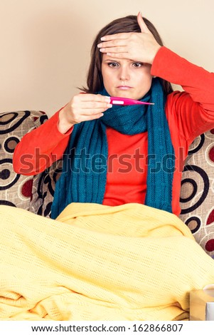 Young woman having flu and  checking  thermometer at home - stock photo
