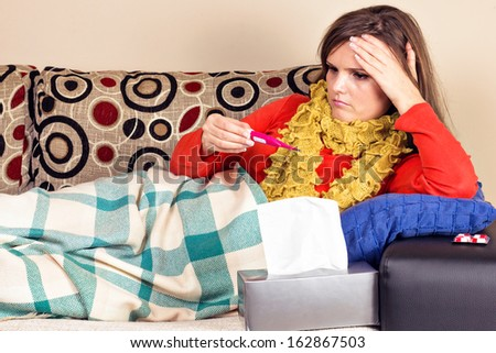 Young woman having flu and taking her temperature at home - stock photo