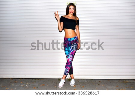 Young woman having fun, fit sexy body, wearing printer sport legging crop top, long brunette hairs, bright make up, urban wall background. - stock photo