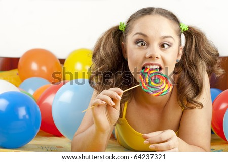 Young woman having fun playing with balloons and goofing around - stock photo