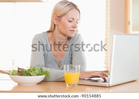 Young woman having healthy lunch while working on her laptop - stock photo