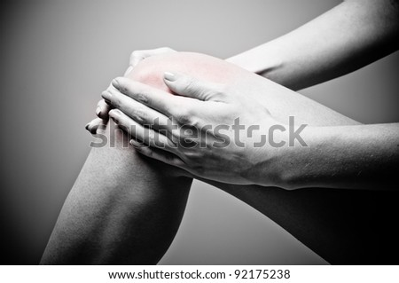 Young woman having knee pain - stock photo