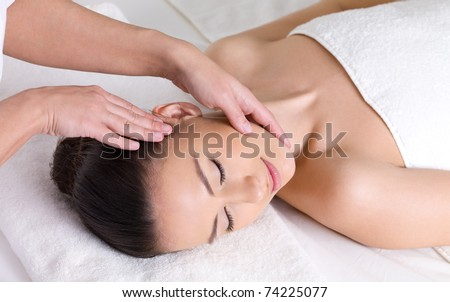 Young woman having massage for the skin of her beautiful face - stock photo